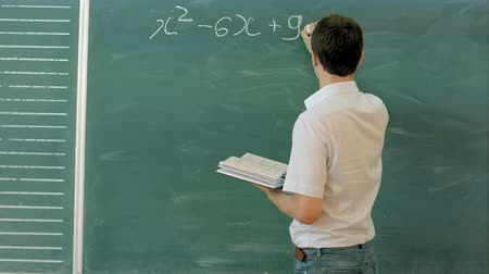 старшей школе : College student writing on the chalkboard during a math class