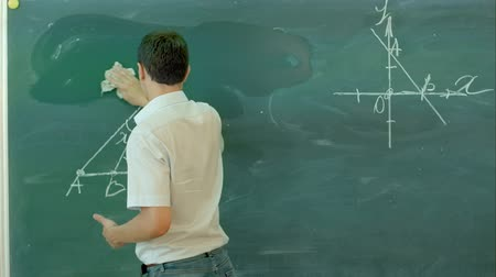 borracha : Male teache washes the chalkboard in classroom Stock Footage