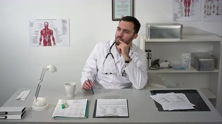 gyógyszerész : Serious bearded doctor sitting in medical office and thinking about treatment