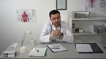 строгий : Medical consultation by bearded doctor seriously talking to camera
