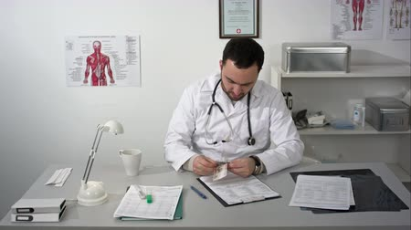 physician : Sad doctor or medic counting his money Stock Footage