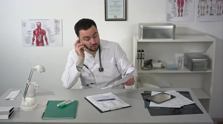 ameaça : Angry doctor or medic swears by phone Stock Footage