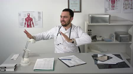 curioso : Happy excited doctor making strange gestures dancing at workplace Vídeos