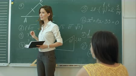középiskola : Pretty young college student by the chalkboard or blackboard during a math class Stock mozgókép