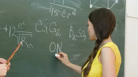 репетитор : Student writing chemical symbol on blackboard.