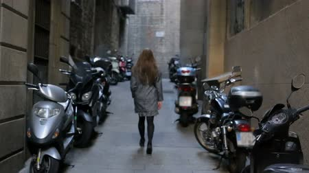 парковка : Young woman walking throught motorcycle parking