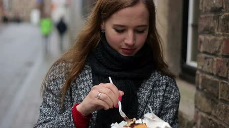 desszertek : Urban portrait of young beautiful female tourist eating belgian waffle on street of Brugge, Belgium. Stock mozgókép