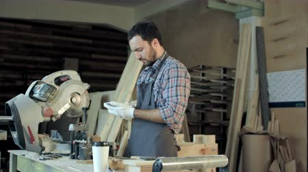 restauração : Carpenter with beard makes something on his smart phone in workshop.