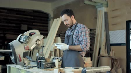restauração : Carpenter standing near electric saw in his workshop and drinking coffee. Stock Footage