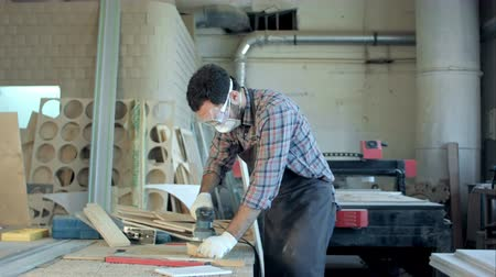 um : Bearded carpenter in safety glasses working with electric planer in workshop.