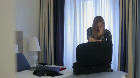 мотель : woman tourist packing a suitcase in hotel