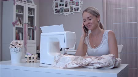 dressmakers : Young woman happily talking on the phone while sitting at the table next to sewing machine