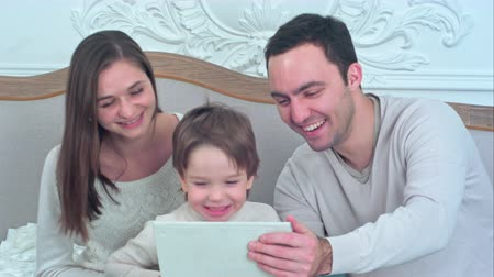 photo album : Young happy family watching their photos on the tablet and laughing Stock Footage