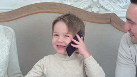 čtyřicet : Smiling little boy talking on the phone surrounded by his happy family