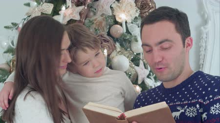 conta : Young father reading Christmas tale, while mother and their happy son whispering secretly