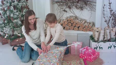 wrapping paper : Happy mother and her little son wrapping up Christmas gifts at home