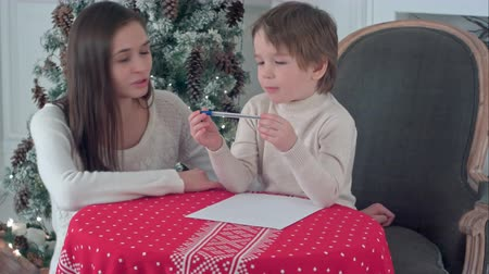 isteyen : Young mother helping her struggling son to write a letter to Santa Claus Stok Video