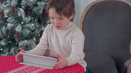 sob : Cute little boy using tablet while sitting on a big armchair at home over Chirstmas tree background