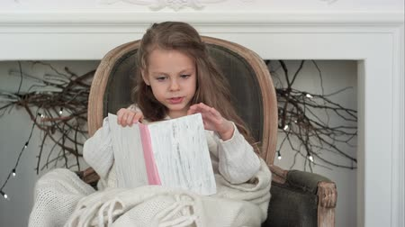 holidays : Lovely little girl wrapped in white Christmas blanket reading a book sitting in an armchair near the decorated fireplace