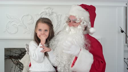 santaclaus : Santa Claus sitting in a chair with a little girl dreaming about her Christmas presents