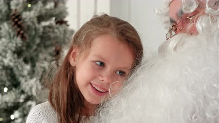 klauzule : Cute little girl singing Christmas song together with Santa Claus Dostupné videozáznamy
