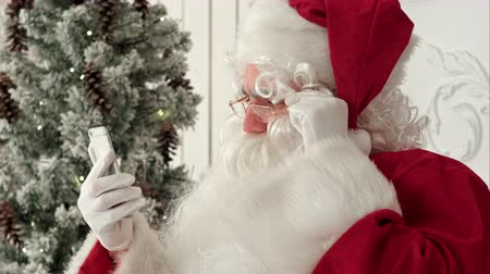 senhor : Happy Santa Claus checking up Christmas emails from kids on his phone