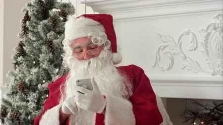 stockings : Happy Santa Claus reading Xmas messages on the phone and smiling while sitting at his chair