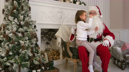 describing : Sweet little girl sitting on Santa lap and describing him what she wants for Christmas
