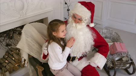 klauzule : Santa Claus sitting in a chair with a little girl dreaming about her Christmas presents