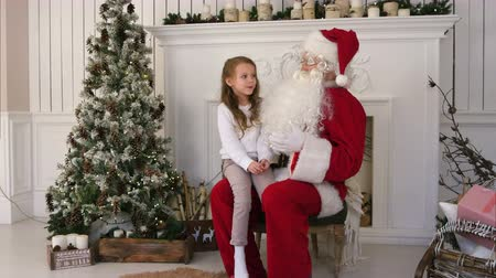 záradék : Cute little girl singing a Christmas song sitting on Santa Claus lap