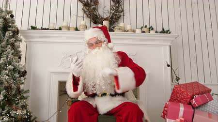 klauzule : Laughing Santa Claus reading Christmas messages from kids