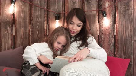 christmas tree with lights : Pretty young mom reading a Christmas tale to her cute daughter sitting on the sofa wrapped in blankets Stock Footage