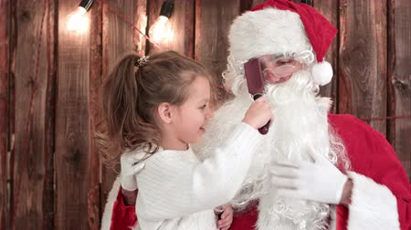 newyear : Little girl sitting on the lap of old Santa and brushing his beard