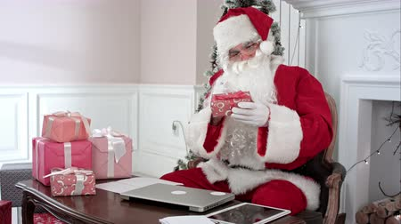 wąsy : Busy Santa Claus preparing presents using laptop and digital tablet, sorting his letters and receiving a gift from a little girl Wideo