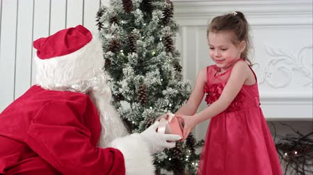 getting : Santa Claus giving present to a surprised little girl and hugging her Stock Footage