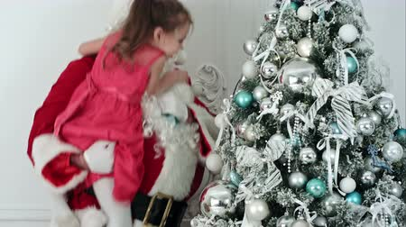 мишура : Fake Santa Claus decorating a Christmas tree holding a little girl in his arm