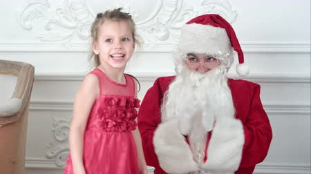 girl claps : Santa Claus clapping his hands while pretty little girl dancing around him