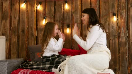 girl claps : Happy mother and daughter playing clapping game on Christmas eve Stock Footage