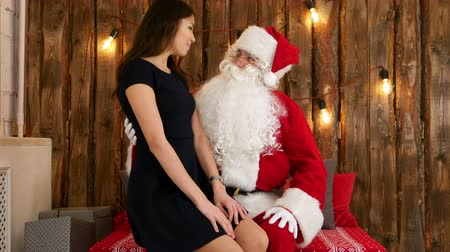 riso : Attractive young brunette sitting on Santa Claus lap and telling her Chistmas wishes