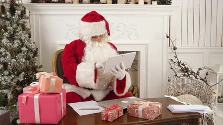 elves : Santa Claus using tablet to give a quick video call to the North Pole Stock Footage