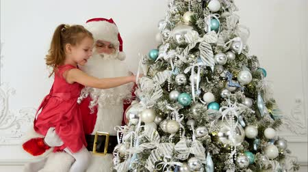 sahte : Santa Claus with pretty little girl decorating Christmas tree Stok Video