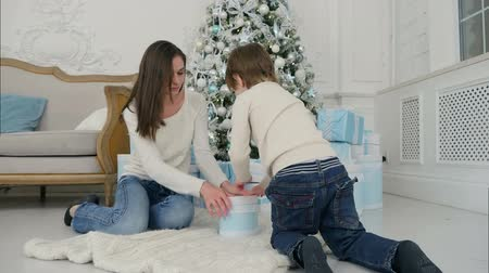 pozlátko : Young mother and happy son putting a gift back into the pile under the Christmas tree Dostupné videozáznamy