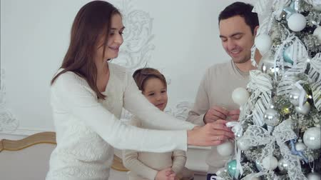 безделушка : Happy family decorating Christmas tree in the living room Стоковые видеозаписи