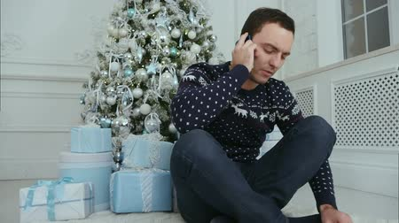 seriously : Young man talking on the phone sitting under the Christmas tree Stock Footage