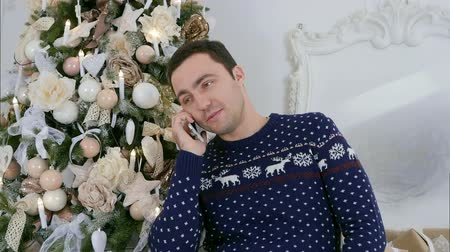 seriously : Young man in Christmas sweater talking on the phone