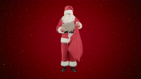 elves : Santa Claus with his sack of lots of presents on red background with snow