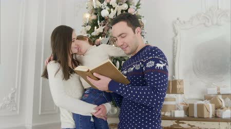 photo album : Happy father reading a Xmas tale while mother holding their cheerful son in front of the Christmas tree