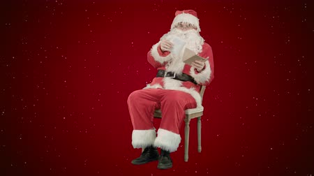 záradék : Santa Claus sitting on chair with letters in hands on red background with snow
