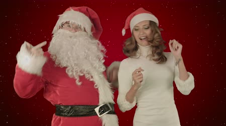 elfo : Santa claus dance with Attractive Christmas lady on red background with snow Stock Footage
