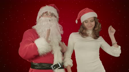 maiden : Santa claus with beautiful dancing girl on red background with snow